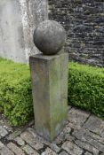 A carved stone garden plinth with weathered spherical finial. H.140cm