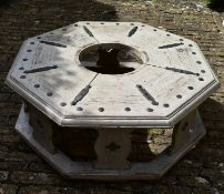 An Octagonal distressed painted wood and iron bound garden bench on platform base. H.50xW.120cm