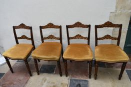 A set of four late 19th century walnut dining chairs with profuse ebony and satinwood inlay to the