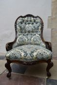 A Victorian mahogany nursing chair with carved and pierced back rail on cabriole supports in deep