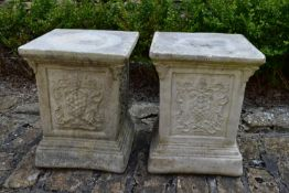 A pair of stepped garden plinths with armorial decoration. H.42xW.34cm