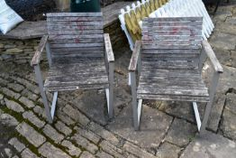 A pair of metal framed weathered teak garden armchairs. H.89xW.66cm