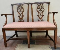 A late 19th century mahogany double chair back settee in the Chippendale style with drop in seat