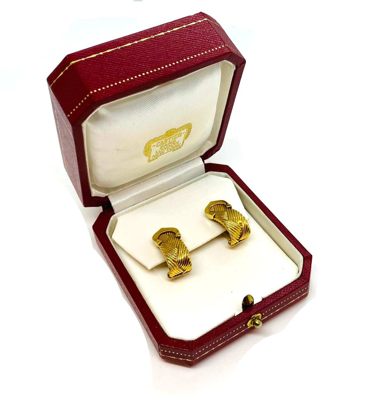 A pair of Vintage Cartier crossed C's textured yellow gold ear clips, mounted in 18ct yellow gold.
