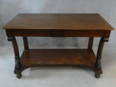 An early 19th century mahogany console table with frieze drawers and shaped and carved front
