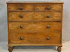 A 19th century mahogany chest of two short over three long graduating drawers on reeded bun feet.