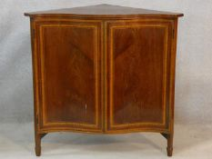 An Edwardian figured mahogany and satinwood inlaid serpentine fronted corner cabinet on square