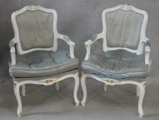 A pair of white painted Louis XV style fauteuils in damask upholstery and fitted squab cushions on