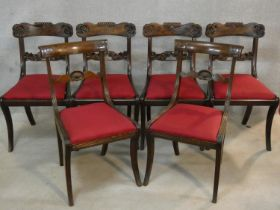 A set of six Regency mahogany bar back dining chairs with shell carving to the backs above drop in