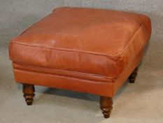 A leather upholstered footstool on turned tapering supports. H.37 W.58 D.58