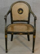 An antique black lacquered and Chinoiserie decorated open armchair with caned back and seat on