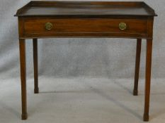 A 19th century mahogany writing table of concave outline fitted with frieze drawer on square