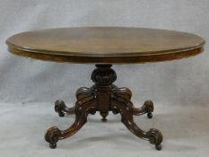 A Victorian burr walnut tilt top dining table on quatreform carved swept supports. H.72 L.137 W.