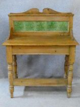 A Victorian pine washstand with Art Nouveau tiled back raised on turned stretchered supports. H.