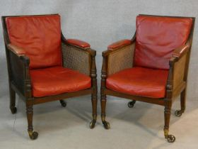 A pair of Georgian mahogany framed library bergere armchairs with leather upholstered seat and