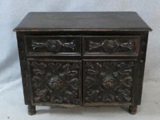 An antique oak side cabinet with carved drawers and doors on circular squat supports. H.73 W.93 D.
