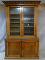 A mid 19th century oak library bookcase with acanthus carved pediment above glazed doors enclosing