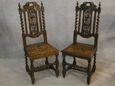 A pair of late 19th century Carolean style hall chairs with carved backs and panel seats on