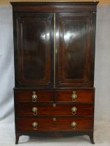 A Regency mahogany linen press with stepped dentil cornice above panel doors enclosing interior