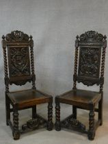 A pair of Continental antique oak hall chairs with crown crestings to the carved backs above panel