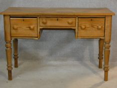 A 19th century pitch pine kneehole writing table with three frieze drawers on turned tapering