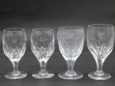 A antique circular etched floral and foliate design crystal decanter with four wine glasses. The