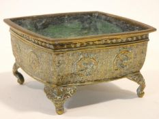 An 18th/19th century Chinese brass engraved square planter on four animal head feet. The sides of