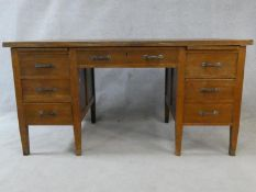 A mid century oak pedestal desk on square tapering supports. H.77 W.153 D.78cm
