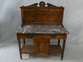 A late 19th century walnut washstand with carved superstructure and veined marble top above a pair