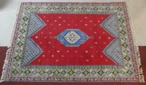 A Persian carpet with central lozenge medallion on madder ground with stylised motifs across the