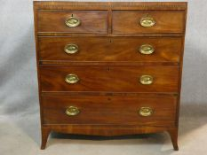 A Regency mahogany chest of drawers with satinwood and ebony chequer inlay and oval brass plate