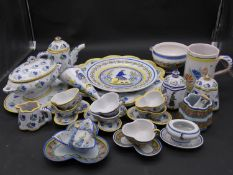 A large collection of antique Adolphe Porquier Quimper hand painted pottery dinner ware. Decorated