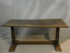 A 19th century oak refectory dining table with planked and cleated top on stretchered platform base.