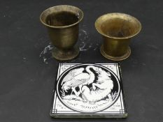 """Two antique brass pestles and a Mintons Aesop's Fable ceramic tile """"Wolf And The Crane"""" Makers stamp"""
