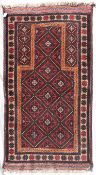 An Afghan Balouch prayer rug with repeating lozenge design within flowerhead border. L.160xW.85cm