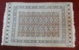 An Eastern woollen rug with repeating lozenge motifs on a beige ground within stylised multiple