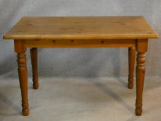 A Victorian style pine kitchen dining table on turned tapering legs. H.74 L.120 W.80cm
