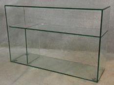 A modernist design plate glass open display side cabinet. H.77 W.118 D.35cm