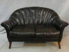 A vintage Tetrad scallop shaped two seater sofa in tobacco leather upholstery on swept supports. H.