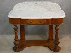 A Victorian mahogany washstand with shaped and veined marble top above frieze drawer and turned