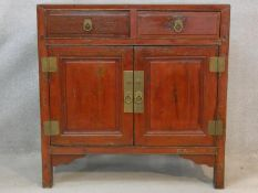 A Chinese hardwood and brass bound side cabinet with frieze drawers above a pair of panel doors on