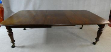 A Victorian mahogany extending dining table with three extra leaves raised on turned tapering
