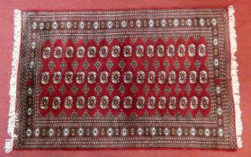 A Bokhara style rug with repeating gul motifs across the madder field enclosed by mutliple geometric
