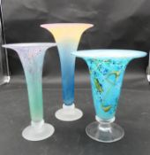 Three studio blown glass trumpet vases, one with a rainbow gradient, one with an abstract pink