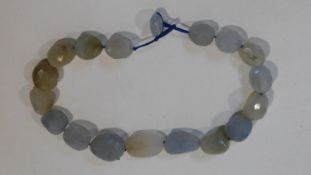 A statement faceted Chalcedony pebble necklace with a silk chord loop clasp. Composed of graduated