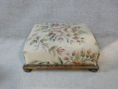 A 19th century mahogany footstool in tapestry upholstery on bun feet. H.16 L.44.5 W.44.5cm