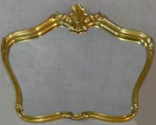 A contemporary shaped gilt frame wall mirror with Rococo shell cresting. H.75 W.102cm