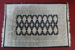An Eastern rug with repeating medallions on a midnight ground within stylised floral multiple