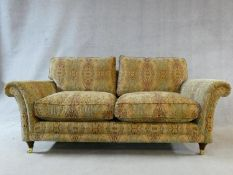 A large Parker Knoll two seater Burghley sofa in Baslow Medalli gold upholstery raised on turned
