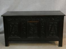 An antique country oak coffer with hinged lid above floral carved panels on block feet. H.75 L.136